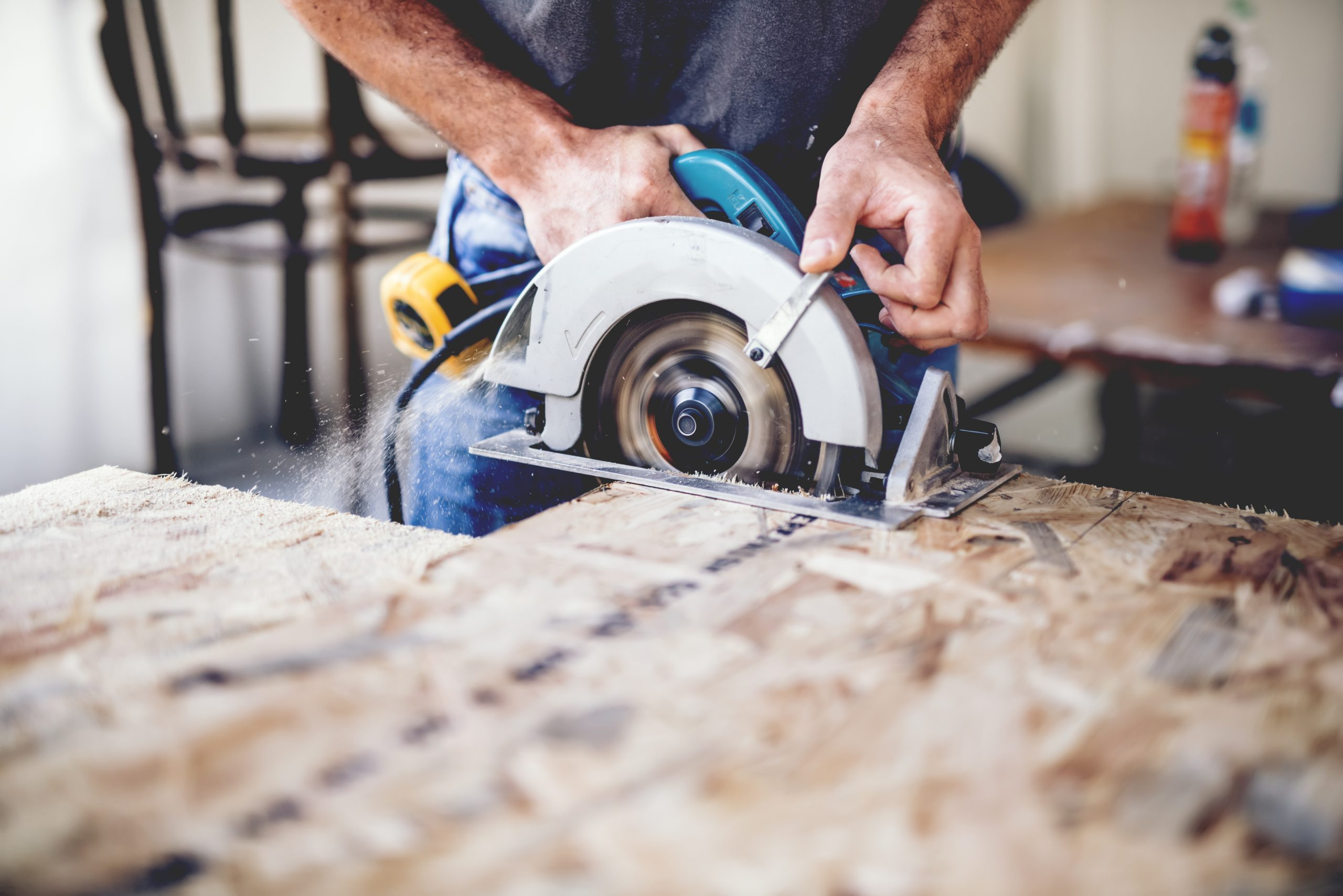 Carpenter using circular saw for cutting wooden boards. Construction details of male worker or handy man with power tools winnipeg